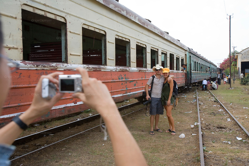 ROYAL CAMBODIAN RAILWAYS. The journey from Phnom Penh to Battambang is the last working route. A passenger train, operates only at weekends. A Czech made diesel locomotive, leaves the capital Saturday morning, arriving in Battambang 22 hours later in the dead of night, and returns on Sunday. Max speed is about 30kmh, often slower due to the track's terrible condition. Carriages are dilapidated, with holes in the floor and only spaces for windows. Passengers sit or sleep on hardwood bench seats, hammocks, or on the floor of cargo carriages. The drivers, controllers & guards add to their small monthly pay by charging for local passengers and cargo; from motor bikes and local produce to timber loaded aboard at the 30 stations along the route. This together with other trains and farm vehicles further slows the journey. In rural areas, the track is a lifeline, and used for local transport on 'bamboo trains' powered by belt-motors, or pushcarts. Boom towns, with a 'goldrush mentality' near the rapidly depleted rainforest, are a hive of activity, with logging as their resource, where children workers even gamble away their earnings on cardgames. In the city, the railway has a life of its own, where people live and work nearby or on the track itself. Market stalls, restaurants, chairs and tables, are removed only briefly, when the infrequent train passes!///Tourists having their picture taken whilst the Czech train stops in Pursat Station