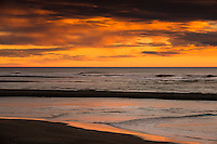 Intense sunset over Tasman Sea at Hokitika River mouth, South Westland, West Coast, New Zealand