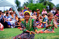 A group of schoolchildren perform a seated hula outdoors on a green lawn at an annual May Day/Lei Day celebration.