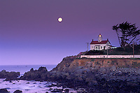 Full moon over the Pacific Ocean in purple sky at dawn, above Battery Point Lighthouse, Crescent City, Northern California Coast.