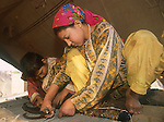 Two Afghan refugee children work making a carpet inside their family's tent in the Shamshatoo refugee camp outside Peshawar, Pakistan..