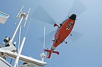 A United States Coast Guard HH-65C Dolphin helicopter hovers above the deck of a Coast Guard Auxiliary vessel. The helicopter and crew, based at U.S. Coast Guard Air Station San Francisco, was on a practice mission with the Coast Guard Auxilary to maintain search and rescue proficiency. Photographed 04/08