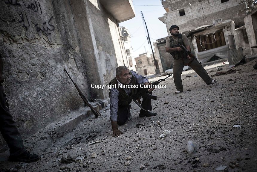 Rebel fighters fire to the enemy position during skirmishes at the first line of fire in Karmal Jabl neighborhood, district of Arkup, at the northeast of Aleppo CIty.