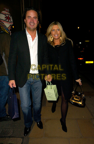 OLI WHEELER & TINA HOBLEY.The Prada Christmas party, Prada Store, Old Bond Street, London, England. .December 13th, 2007.full length married husband wife couple black coat jacket goody bag jeans denim purse.CAP/CAN.©Can Nguyen/Capital Pictures