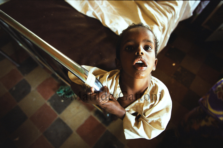 Eritrea - Gash barka - Little boy suffering from severe malnutrition at the hospital. As a result of 30 years of war for independence against Ethiopia (from 1961 to 1991) and another 3 years from 1997 to 2000, there are 50,000 Eritreans currently living in internally displaced (IDP) camps throughout the country. These IDPs have fled three times in the last 10 years, each time because of renewed military conflict. They lived in relatives' homes when lucky enough, but mostly, the fled to the mountains, where they attempted to do what Eritreans do best, survive. Currently there is no Ethiopian occupation in Eritrea, but landmines prevent the IDPs from finally going home. .It is estimated that every Eritrean family lost two or three members to the war which makes the reality of the current emergency situation even more painful for Eritreans worldwide. Currently, the male population has been decreased dramatically, affecting the most fundamental socio-economic systems in the country. Among the refugee population, an overwhelming majority of families are female-headed, severely affecting agricultural production. For, IDPs in particular, 80% of households are female-headed..The unresolved border dispute with Ethiopia remains the most important drawback to Eritrea's socio-economic development, as national resources (human and material) continue to be prioritized for national defense. Eritrea is vulnerable to recurrent droughts and variable weather conditions with potentially negative effects on the 80 percent of the population that depend on agriculture and pastoralism as main sources of livelihood. The situation has been exacerbated by the unresolved border dispute, resulting in economic stagnation, lack of food security and increased susceptibility of the population to various ailments including communicable diseases and malnutrition..
