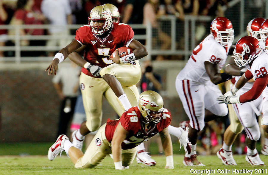 TALLAHASSEE, FL 9/17/11-FSU-OU091711 CH-Florida State's EJ Manuel hurdles over David Spurlock during first half action against Oklahoma Saturday at Doak Campbell Stadium in Tallahassee. .COLIN HACKLEY PHOTO