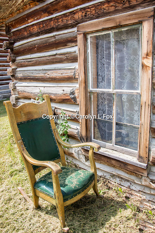 An old green chair sits outside an old building that has a lace curtain hanging at the window.