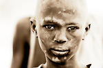 A Dinka boy grows up in a cattle camp in Eastern Rumbek, South Sudan. The Dinka are the primary ethnic group in South Sudan. Traditionally pastoralists, they live in camps with hundreds or even thousands of cows.  The white marks on the boy's face are cow dung ash, which serves as both a cosmetic and insect repellent.