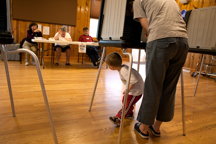 Poll worker Elaine Miller, center, waves to Elliott Jennings, three, as his mom Gayle votes at Buffalo Hart Presbyterian Church, in Buffalo, Ill., on primary day. Poll workers Brenda Coss and Mike Thompson are at left and right.