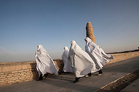 A group of women, dressed in white chadors, crossing the Varzaneh bridge. Traditionally, in the region, white is worn to ward off evil.