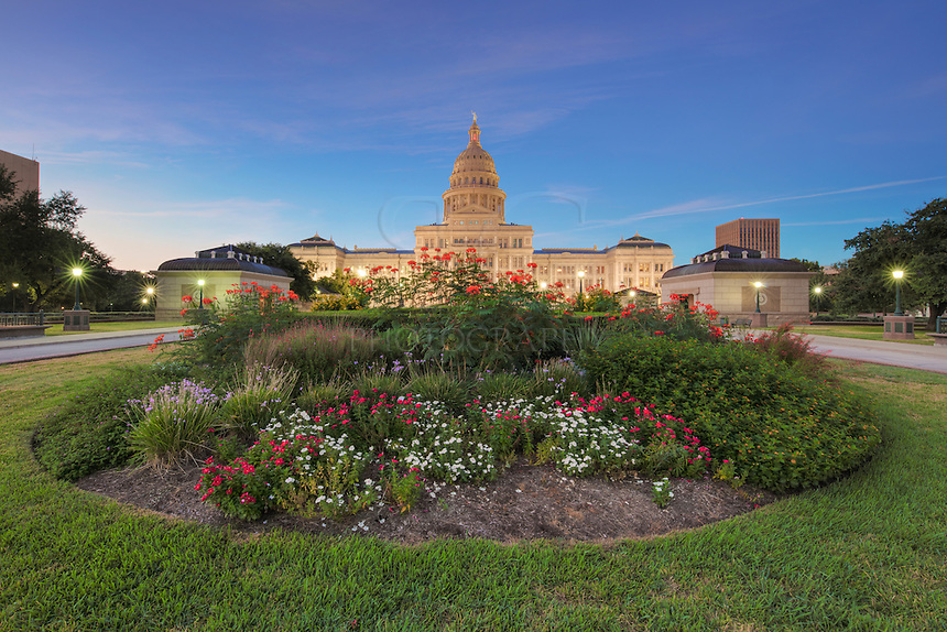 On a mild September morning, the historic Texas State Capitol glows in the pre-dawn hours in downtown Austin. In the foreground rests one of the many gardens on the 22 acre complex. The Capitol building itself takes up 2.5 acres, and on the surrounding land are trees, grass, rose gardens, and over 20 monuments commemorating important times and figures in Texas History.