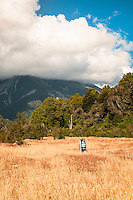 Female hiker on grassy clearing aside of Perth River, South Westland, West Coast, New Zealand