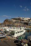Hotels overlooking harbour and boats at Puerto Rico, Gran Canaria, Canary Islands, Spain.