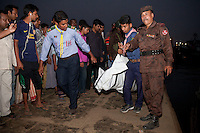 Bangladeshi rescue workers lift the dead body of one of the victims after a river ferry carrying about 100 passengers capsized in the River Padma Sunday after being hit by a cargo vessel at Paturia, in Manikganj district, about 80 kilometers  northwest of Dhaka, Bangladesh. Feb. 22, 2015