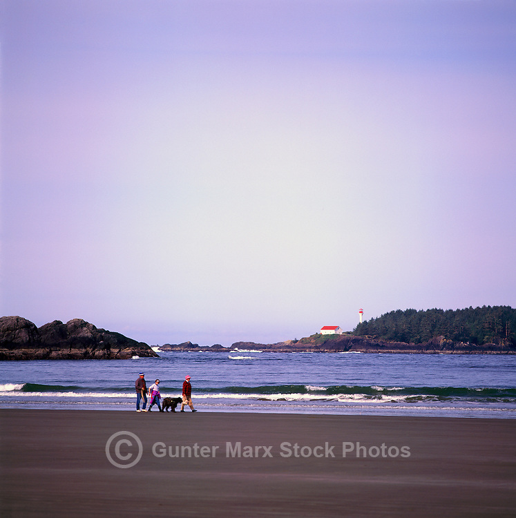 Seniors walking on Chesterman Beach near Pacific Rim National Park Reserve, on West Coast of Vancouver Island, BC, British Columbia, Canada - Lennard Light in background