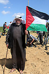 A Palestinian man holds his national flag as Palestinians plant olive trees to mark Land Day during a symbolic ceremony held in the village of Abassan, east of Khan Yunis near the border fence between Israel and the southern Gaza Strip on March 31, 2015. On the annual Land Day, demonstrations are held to remember six Arab Israeli protesters who were shot dead by Israeli police and troops during mass protests in 1976 against plans to confiscate Arab land in the Galilee. Photo by Abed Rahim Khatib