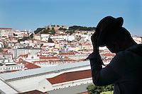 Man admiring the view of Lisbon with St George's Castle or Castelo de Sao Jorge, from the Miradouro Sao Pedro de Alcantara, Lisbon, Portugal. The viewpoint is situated in a garden accessed via the Gloria Funicular or Ascensor da Gloria or Elevador da Gloria, inaugurated in 1885. The tram is listed as a National Monument. Picture by Manuel Cohen