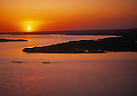Aerial view looking West into the sunset over the lower James River at historic Jamestown Island on right. Two barges are passing by Jamestown at center left.  The Colonial National Historical Park (U.S. National Park Service,) is in Virginia's &quot;Historic Triangle&quot; operates Jamestown Island.