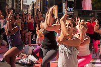 "Thousands of yoga practitioners pack Times Square in New York to participate in a Power Yoga class on the first day of summer, Saturday, June 21, 2014. The 12th annual Solstice in Times Square, ""Mind Over Madness"",  stretches the yogis' ability to block out the noise and the visual clutter that surround them in the Crossroads of the World. (© Richard B. Levine)"
