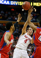 Ohio State Buckeyes guard Aaron Craft (4) gets a pass by Dayton Flyers guard Vee Sanford (43) and Dayton Flyers forward/center Jalen Robinson (12) in the first half of the second-round NCAA Tournament game between the Ohio State Buckeyes and the Dayton Flyers at the First Niagara Center, Thursday afternoon, March 20, 2014. The Dayton Flyers defeated the Ohio State Buckeyes 60 - 59. (The Columbus Dispatch / Eamon Queeney)