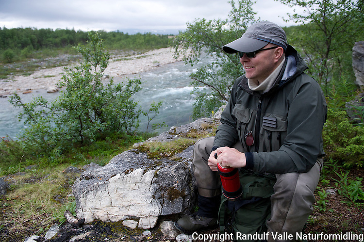 Mann med termos ved Storelva i Lebesby. ----- Man with thermos flask.