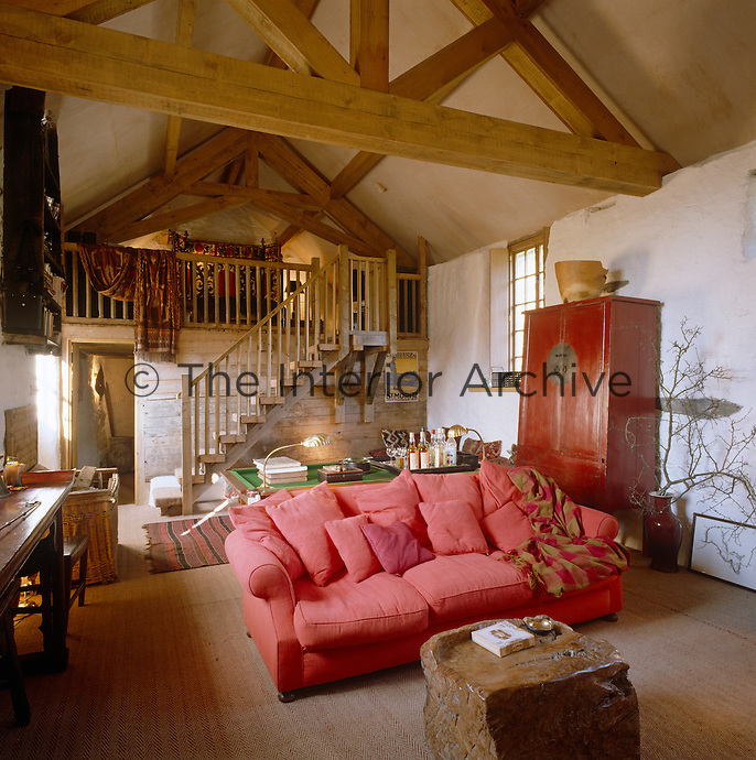 The massive oak beams and rough-hewn walls of the living room betray the origins of the living room, while a galleried bedroom has been created out of the hayloft