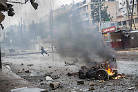 In this Monday, Dec. 17, 2012 photo, a man runs for cover as smoke rises from a car in fire after a mortar shell landed on a commercial street killing two people in the Bustan Al-Qasr district of Aleppo, Syria. (AP Photo/Narciso Contreras)