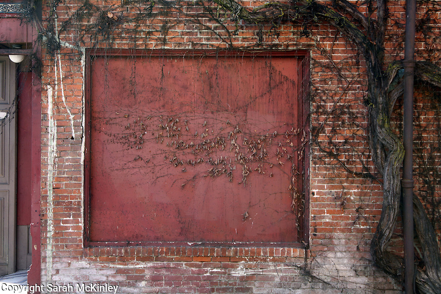 Vines frame and crawl across a large, boarded-up, square window on the Palace Hotel in Ukiah in Mendocino County in Northern California.