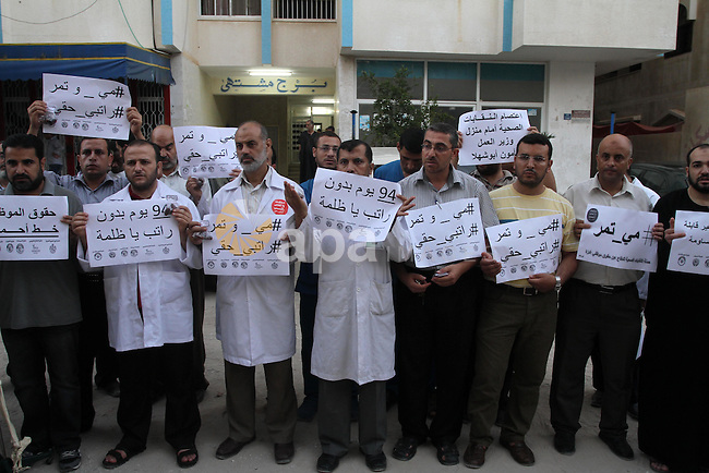 Palestinian employees of the former government in Gaza Strip hold placards during a protest against not receiving their salaries, in front of the home of Minister of Labor Mamoun Abu Shahla, in Gaza City on July 03, 2014. Many issues involving the Strip, such as the fate of former employees of the Hamas government, have yet to be addressed by the new unity government. Photo by Mohammed Asad