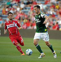 Portland midfielder Jack Jewsbury (13) dribbles away from Chicago midfielder Daniel Paladini (11).  The Portland Timbers defeated the Chicago Fire 1-0 at Toyota Park in Bridgeview, IL on July 16, 2011.