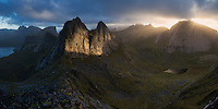 Rays of light illuminate Kråkhammartind (732m) from summit of Markan (602m), Moskenesøy, Lofoten Islands, Norway