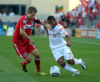 Toronto forward Joao Plata (7) takes a hand to the face from Chicago midfielder Logan Pause (12).  The Chicago Fire defeated Toronto FC 2-0 at Toyota Park in Bridgeview, IL on August 21, 2011.