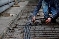 Plant History Glasshouse (formerly Australian Glasshouse), 1830s, Rohault de Fleury, Jardin des Plantes, Museum National d'Histoire Naturelle, Paris, France. Detail of renovation works: a builder prepares a floor for laying concrete slabs.