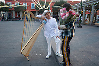 A Jarocho singer chats with a flower vendor in Plaza Garibaldi where Mariachis gather to be hired in Mexico City, Friday, Jan. 4, 2008