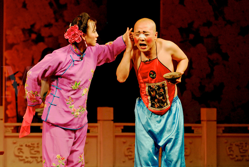 Traditional Chinese comedy skit, Rolling Lamp, at the Sichuan Opera, Chengdu. China.  A scolding wife tweaks the ear of her disobedient husband.