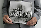 Sunao Tsuboi holds a photograph, by photographer Yoshito Matsushige, taken on Miyuki Bridge 3 hours after the atomic bombing of Hiroshima. This was the first photo taken after the bombing, and shows Sunao Tsuboi sitting injured on the bridge. Hiroshima, Japan, 21.07.2005