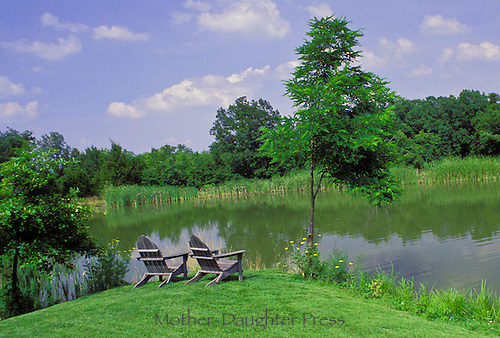 Two adirondack chairs stit at the point of land overlooking a lake in summer