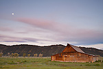 The pastel light from sunrise paints gorgeous colors above this barn in Mormon Row with the moon shining above.