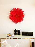 A bright scarlet 3D artwork creates a bold splash of contrast on the white wall of one of the bedrooms