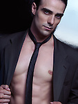 Portrait of a sexy young man wearing a necktie and a jacket over bare muscular torso