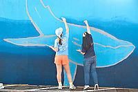 UCLA volunteers LeeAnn Patrick (left) and Isabella Europa paint Janet Wallace's ocean themed mural at the Santa Monica Pier on Saturday, January 28, 2012.