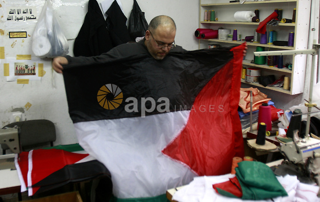 A Palestinian man sews his national flag at his workshop in the West Bank city of Nablus, Monday, Nov. 14, 2011. during the preparation to mark the anniversary of the declaration of independence state of Palestinian on November 15. Photo by Wagdi Eshtayah