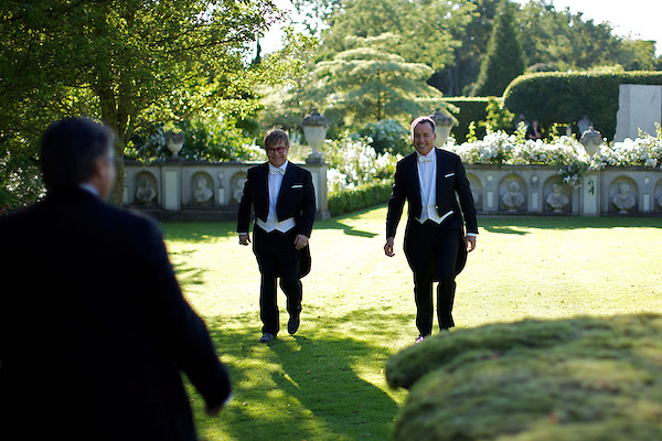 Elton John and David Furnish walk across the lawn of Elton John's house at the Beginning of The White Tie and Tiara Ball