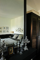 The black and white master bedroom is reflected in a large mirror hanging above the fireplace
