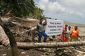A family living next to the sea in the village of Tenoraereke, stand with Greenpeace Climate Change campaigner Koin Etuati (on right of picture), on the Pacific island of Kiribati, beside some collapsed coconut trees, fallen over due to sea erosion of the land.