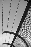 Prison-like barbed fencing along the pdestrian walkway on Sydney Harbour Bridge prevents people from accessing the roadway or jumping off the bridge