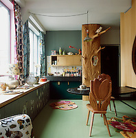 The predominately green kitchen contains some interesting carved wood pieces including a hat stand and a chair