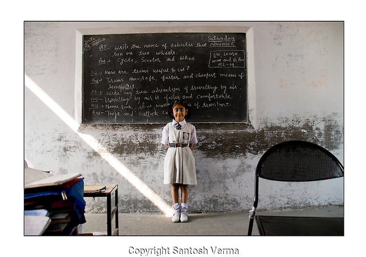 A girl student in a rural school in India brightens the class with her confident posture, smile and demeanor as a ray of sunlight falls naturally at her feet. Photograph © Santosh Verma