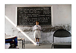 A girl student in a rural school in India brightens the class with her confident posture, smile and demeanor as a ray of sunlight falls naturally at her feet. Photograph &copy; Santosh Verma