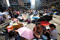 HONG KONG, HONG KONG SAR, CHINA - SEPTEMBER 30: Protestors sit under umbrellas to protect themselves from the sun, as part of a pro-democracy sit-in known as 'Occupy Central', blocking traffic on Hennessy Road, an otherwise busy multi-lane thoroughfare in Causeway Bay, Hong Kong, on September 30, 2014. Now sometimes named the 'Umbrella revolution', the Occupy Central civil disobedience movement began in response to China's decision to allow only Beijing-vetted candidates to stand in the city's 2017 election for the top civil position of chief executive. (Photo by Lucas Schifres/Getty Images)
